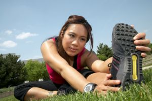 Woman stretching in a field before running.